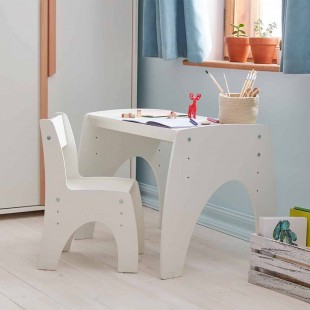 Petite table réglable blanche dans une chambre bébé avec chaise